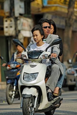 Asia, Vietnam, Hanoi. Hanoi old quarter. Vietnamese family riding on motorbike through Hanoi.