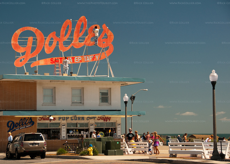 Workers repaint and overhaul the Dolles sign as the boardwalk and beach begin to fill with summer visitors and beachgoers.  The landmark sign above Dolles Salt Water Taffy is a landmark at the intersection between the beach boardwalk and the end of Rehoboth Avenue in Rehoboth Beach, Delaware, USA.