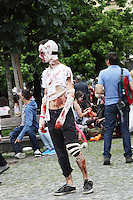 Male participant in the prague zombie walk, wrapped in bandages, wearing dark blue jeans and sneakers.