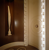 A modern sculpture is displayed in an alcove in this small circular hallway