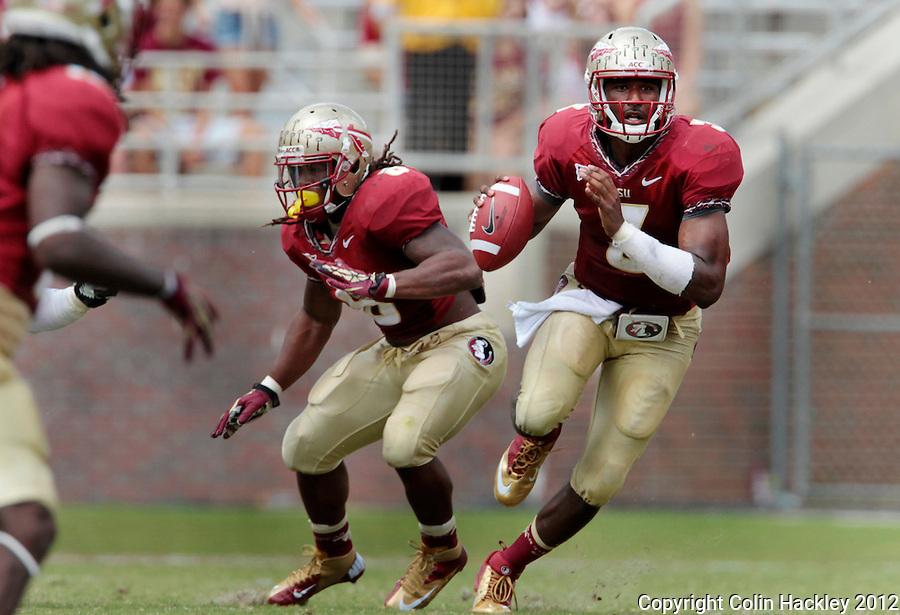 TALLAHASSEE, FL 9/15/12-FSU-WAKE091512 CH-Florida State's EJ Manuel scrambles as Devonta Freeman, left, protects against Wake Forest during second half action Saturday at Doak Campbell Stadium in Tallahassee. .COLIN HACKLEY PHOTO