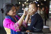 Switzerland. Basel. St. Jakobshalle. A tibetan mother holds a baby bottle to her son drinking water. The family came to Basel for the visit of His Holiness the Dalai Lama. 7.02.2015 © 2015 Didier Ruef