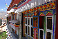 Painted windows in traditional Tibetan style and roof-top prayer flags at the Dhood Gu hotel, looking down onto the Barkhor alleys, Lhasa, Tibet.