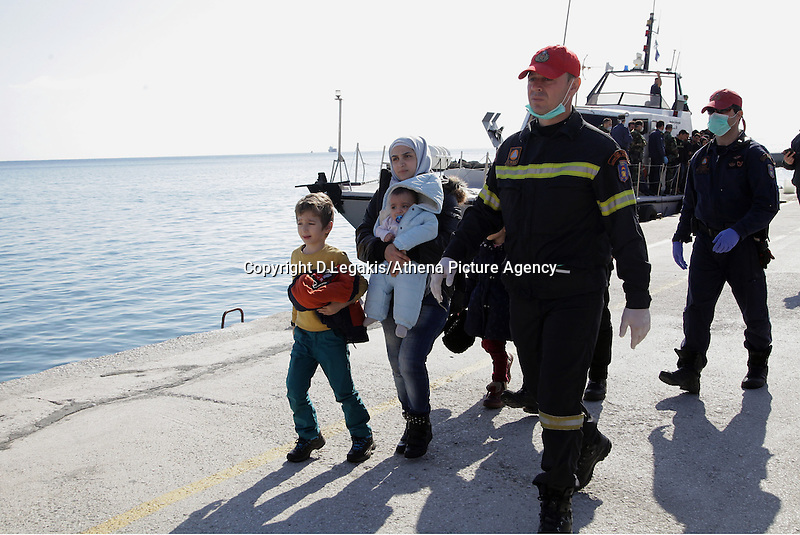 Pictured: A young mother is escorted to safety by a member of the emrgency services Thursday 27 November 2014<br /> Re: One of the largest refugee boats in recent months has disembarked refugees in Ierapetra, Crete. The freighter Baris, carrying 700 people thought to be from Syria and Afghanistan, is being towed by a Greek frigate.<br /> Officials and Red Cross volunteers prepared an indoor basketball stadium as interim shelter in the southern Cretan port town of Ierapetra on Wednesday ahead of the migrants' expected arrival.<br /> Greek officials said the Baris, which lost propulsion on Tuesday, was being towed slowly in poor sea conditions and would arrive after nightfall, probably early Thursday.<br /> They said it was unclear which Mediterranean location had been the departure point for the 77-meter (254-foot) vessel, which was sailing under the flag of the Pacific nation of Kiribati.