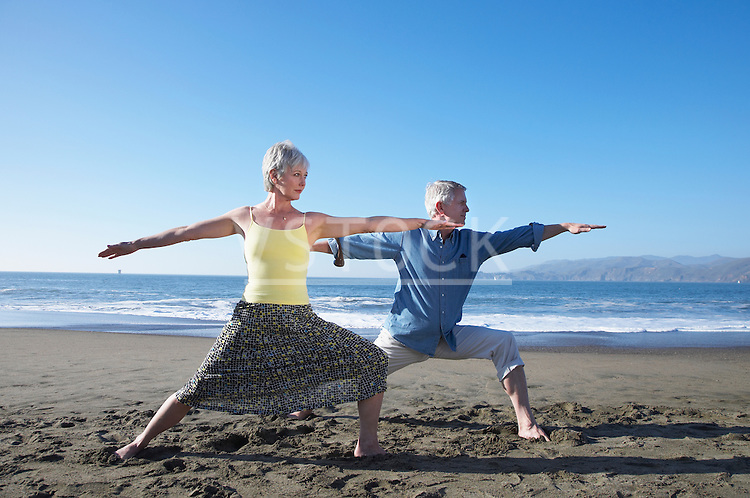 USA, California, Fairfax, Mature couple in warrior yoga pose on beach