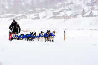 Lance Mackey runs down the Yukon river with the village checkpoint of Ruby in the background in Interior Alaska during the 2010 Iditarod