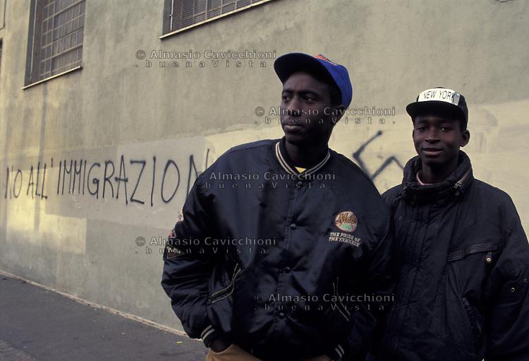 Milano, immigrati africani davanti a una scritta anti immigrazione. Ott. 1990<br /> Milan, African immigrants and an anti-immigration writing on a wall.