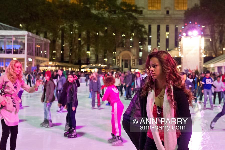 Manhattan, New York, U.S. 9th November 2013. Visitors ice skate and shop at the annual Holiday Shops, at Winter Village skating rink at Bryant Park at night.