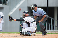 Charlotte Knights catcher Kevan Smith (32) sets a target as home plate umpire Derek Mollica looks on during the game against the Gwinnett Braves at BB&T BallPark on July 3, 2015 in Charlotte, North Carolina.  The Braves defeated the Knights 11-4 in game one of a day-night double header.  (Brian Westerholt/Four Seam Images)