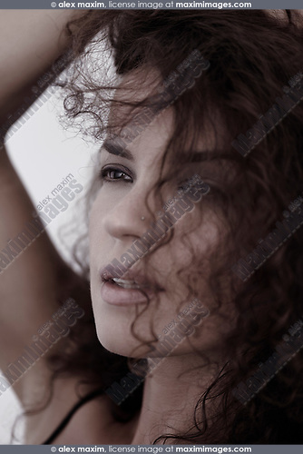 Candid upclose beauty portrait of a young woman face with expressive brown eyes gazing at the distance and long curly dark hair falling on her beautiful face