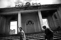 """Nagorny-Karabach, 16.05.2011, Shushi. Zwei M?nner gehen an einem im Krieg v^llig zerst^rten repr?sentativen Geb?ude vorbei. """"The Twentieth Spring"""" - ein Portrait der s¸dkaukasischen Stadt Schuschi, 20 Jahre nach der Eroberung der Stadt durch armenische K?mpfer 1992 im B¸gerkrieg um die Unabh?ngigkeit Nagorny-Karabachs (1991-1994). Two men are walking by a war ruined public house in Shushi. ..""""The Twentieth Spring"""" - A portrait of Shushi, a south caucasian town 20 years after its """"Liberation"""" by armenian fighters during the civil war for independence of Nagorny-Karabakh (1991-1994). .Deux hommes marchent devant la ruine d'un batiment officiel. """"Le Vingtieme Anniversaire"""" - Un portrait de Chouchi, une ville du Caucase du Sud 20 ans après sa «libération» par les combattants arméniens pendant la guerre civile pour l'indépendance du Haut-Karabakh (1991-1994).. © Timo Vogt/Est&Ost, NO MODEL RELEASE !!"""