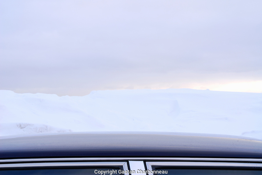 Car rooftop against snow and cloudy sky