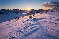 Winter sun shines on snowy slopes of Hoven, Gimsøy, Lofoten Islands, Norway