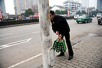 A man carries shopping bags while waiting for a bus in Nanjing, Jiangsu, China.