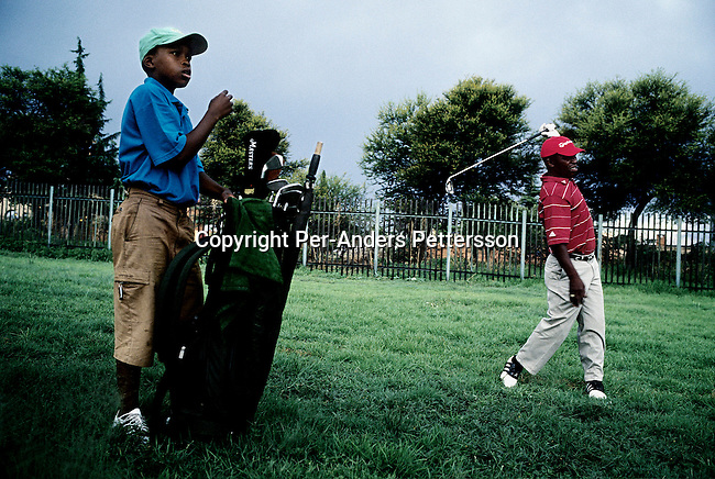 SOWETO, SOUTH AFRICA An unidentified man plays golf with a young boy as caddie at the Soweto Country Club in Soweto outside Johannesburg, SA. A growing number of people belong to the new black elite in the country. Well educated and connected, they have risen from the poverty in the townships to a very different lifestyle, since the fall of Apartheid and the start of democracy in the country in 1994. (Per-Anders Pettersson)