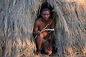 Botswana, Kalahari, bushman (San) with bow and arrow in entrance of grass hut