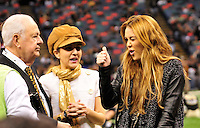 Actor and singer Miley Cyrus hangs out on the Saints sidelines and poses with Saints owner Rita Benson Leblanc and Tom Benson prior to the kick off against the St. Louis Rams.The New Orleans Saints play the St. Louis Rams in New Orleans at the Super Dome Sunday Dec. 12,2010.  Saints were winning 21-6 at half time.Photo©SuziAltman.