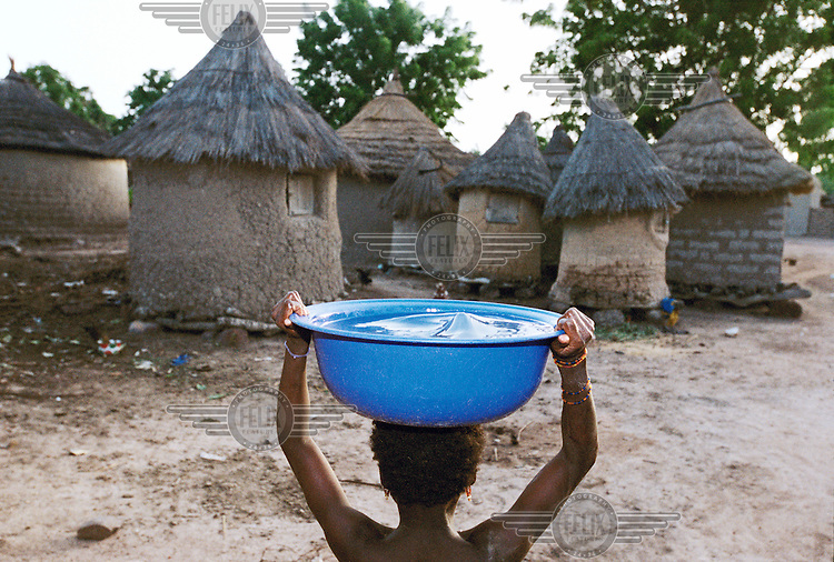 Woman carrying water home on her head. The women collect 20 litres of water at a time, which weighs 20kg.