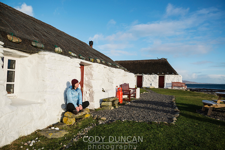Worman sits infront of thatched roof traditional blackhouse now used as youth hostel, Berneray, Outer Hebrides, Scotland