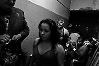 "A female Lucha libre wrestler Sahori walks out in the backstage for her fight at a local arena in Mexico City, Mexico, 30 April 2011. Lucha libre, literally ""free fight"" in Spanish, is a unique Mexican sporting event and cultural phenomenon. Based on aerial acrobatics, rapid holds and the use of mysterious masks, Lucha libre features the wrestlers as fictional characters (Good vs. Evil). Women wrestlers, known as luchadoras, often wear bright shiny leotards, black pantyhose or other provocative costumes. Given the popularity of Lucha libre in Mexico, many wrestlers have reached the cult status, showing up in movies or TV shows. However, almost all female fighters are amateur part-time wrestlers or housewives. Passing through the dirty remote areas in the peripheries, listening to the obscene screams from the mainly male audience, these no-name luchadoras fight straight on the street and charge about 10 US dollars for a show. Still, most of the young luchadoras train hard and wrestle virtually anywhere dreaming to escape from the poverty and to become a star worshipped by the modern Mexican society."