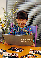 HISPANIC GIRL ENJOYS LOOKING THROUGH A PHOTO ALBUM. HISPANIC GIRL. SAN FRANCISCO CALIFORNIA USA.