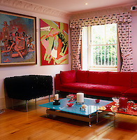 A blue-red coffee table designed by Ab Rogers in an informal sitting room with paintings by George Condo and Lisa Ruyter