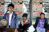 Bangladeshi boys wait at a bus stop in Whitechapel, London, in front of posters advertising an Anti-Nazi League carnival.