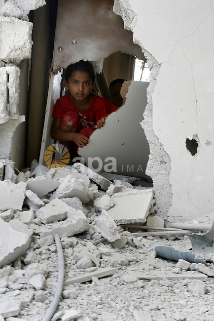 """A Palestinian girl searches in a destroyed house in Khan Yunis in the southern Gaza Strip on September 11, 2014. Israel's deputy foreign minister,Tzahi Hanegbi , warned that Hamas was likely to resume """"violence"""" if it feels it has made no political gains from upcoming talks in Cairo. Photo by Abed Rahim Khatib"""