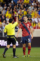 Carlos Bocanegra (5) of the United States gets a yellow card from referee Joel Aguilar . The men's national team of the United States (USA) was defeated by Ecuador (ECU) 1-0 during an international friendly at Red Bull Arena in Harrison, NJ, on October 11, 2011.