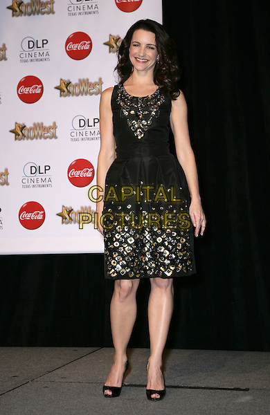 KRISTIN DAVIS .SHOWEST Final Night Talent Awards at the Paris Resort Hotel and Casino,  Las Vegas, Nevada , USA,.18th March 2010..full length black dress gold metal studs embellished rivets sleeveless peep toe Christian Louboutin shoes smiling .CAP/ADM/MJT.© MJT/AdMedia/Capital Pictures.