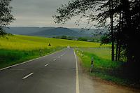 Car driving along country lane under cloudy leaden sky. Crop of oil seed rape in adjoining fields. Aschaffenburg area, Germany.