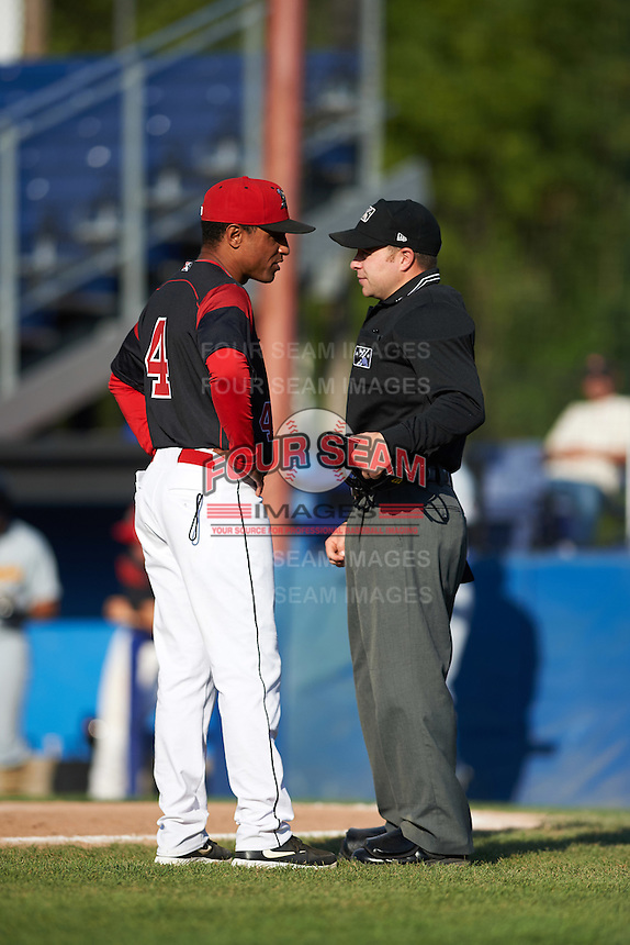 Batavia Muckdogs manager Angel Espada (4) argues a call with umpire John Budka during a game against the West Virginia Black Bears on August 21, 2016 at Dwyer Stadium in Batavia, New York.  West Virginia defeated Batavia 6-5. (Mike Janes/Four Seam Images)