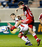 Chicago Fire defender Gonzalo Segares (25) kicks the ball away from New England Revolution midfielder Clint Dempsey (2).  The Chicago Fire defeated the New England Revolution 2-1 in the quarterfinals of the U.S. Open Cup at Toyota Park in Bridgeview, IL on August 23, 2006...
