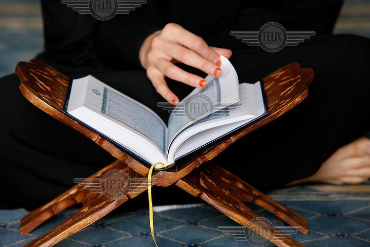 A woman reads a Koran.