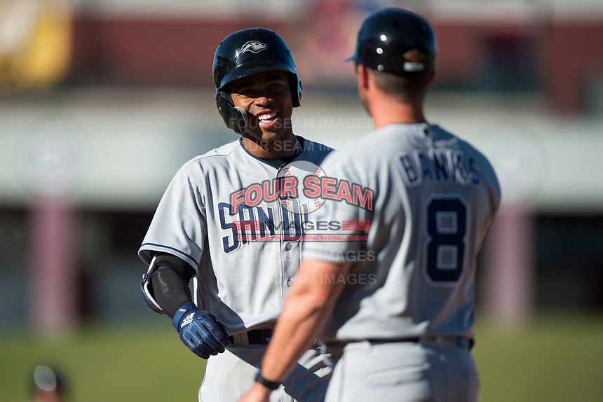 Peoria Javelinas right fielder Buddy Reed (85), of the San Diego Padres organization, jokes with hitting coach Doug Banks (8) after reaching base during an Arizona Fall League game against the Mesa Solar Sox at Sloan Park on November 6, 2018 in Mesa, Arizona. Mesa defeated Peoria 7-5 . (Zachary Lucy/Four Seam Images)