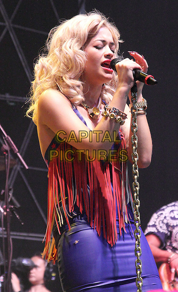 Rita Ora.V Festival 2012 - Day Two, Hylands Park, Chelmsford, Essex, England..August 19th 2012.on stage in concert live gig performance music half length orange red fringed purple leather dress stars print    singing.CAP/JIL.©Jill Mayhew/Capital Pictures