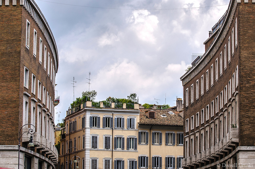 Fine Art Landscape Print Photograph. The dramatic lighting and cloud formations of this photograph, emphasizes the architectural design of many of the buildings in Rome, Italy. <br /> In this photograph the buildings are built to follow the curves of the street. The outer curve of the building on the left looks like it could exactly fit into the inner curve of the building on the right.