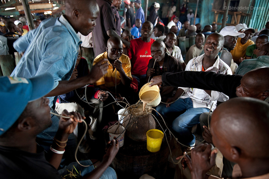 A group of Kenyans dance and drink Busaa, a traditional fermented beer, in a crowded Busaa club at midday in a Nairobi slum on April 7, 2013. Busaa is made by crudely fermenting maize, millet, sorghum or molasses. At Kshs 35 per liter it is much cheaper than a Kshs120 half-liter bottle of commercial beer. The local brew was legalised in 2010 and since then Busaa clubs have become increasingly popular in slums and rural areas. Drinking is on the rise in Kenya, especially among young people. Photo by Benedicte Desrus