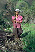 A young woman works on her family's hillside smallholding .