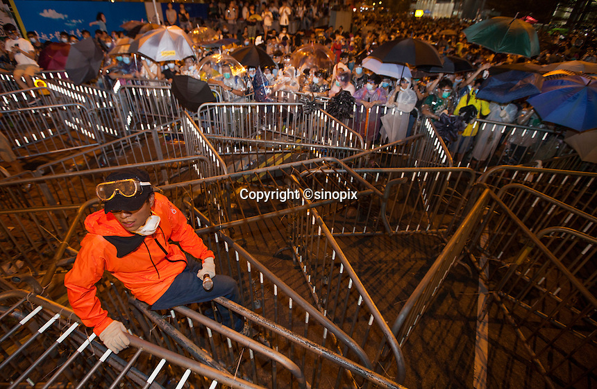 Student protestors man the barricades at an overnight mass sit-in in front of Hong Kong's Central government offices, Hong Kong, China, 28 September 2014. It was announced at the student protest that the society-wide mass disobedience campaign, Occupy Central would commence immediatley - three whole days earlier than was previously forecast. The students and the Occupy Central supporters are protesting the slow pace of democratic reform imposed by the Chinese government on the Hong Kong people.