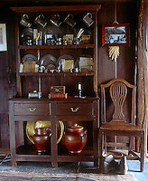 A collection of pewter plates and tankards is displayed on the two-stage cupboard in the living area
