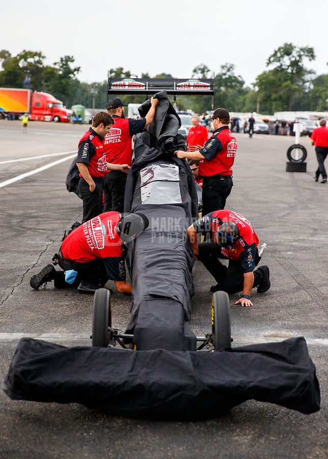 Aug 18, 2017; Brainerd, MN, USA; Crew members for NHRA top fuel driver Leah Pritchett put a rain cover on the dragster during qualifying for the Lucas Oil Nationals at Brainerd International Raceway. Mandatory Credit: Mark J. Rebilas-USA TODAY Sports