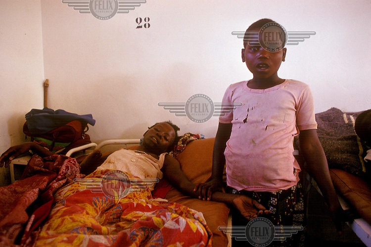 Girl with her dying mother in 'Salle 4', an AIDS ward in the Central Hospital.