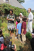 United States First Lady Michelle Obama, left, and chef Dan Barber, right, greet children working in the herb garden as she tours Stone Barns Center Pocantico Hills, New York on Friday, September 24, 2010 with a large group of other First Ladies visiting New York for the United Nations General Assembly. They viewed the mobile chicken coop and herb garden while making a tour of the facilities.  A lunch was prepared with the food from the farm.  Also visible in the photo is Hayrunnisa Gul of Turkey at center..Credit: Andrea Renault / Pool via CNP
