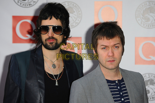 KASABIAN - Tom Meighan & Serge Pizzorno.Arrives at the Q Awards 2010, Grosvenor House Hotel, Park Lane, London, England, UK, October 25th, 2010..arrivals portrait headshot grey gray blue navy white striped beard facial hair black jacket band group necklaces .CAP/CJ.©Chris Joseph/Capital Pictures.