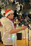 Huntington, New York, USA. February 20, 2014. MEREDITH NUSSBAUM reads her original poem from a cell phone during her Spoken Word  performance at the Jingle Boom Holiday Bash, which also had music, windows decorated by artists. Nussbaum wore a Santa hat and fuzzy white sweater with twinkling Christmas lights, and prizes were given to people wearing the most creative or Ugly Sweaters, at the Main Street Gallery of Huntington Arts Council.