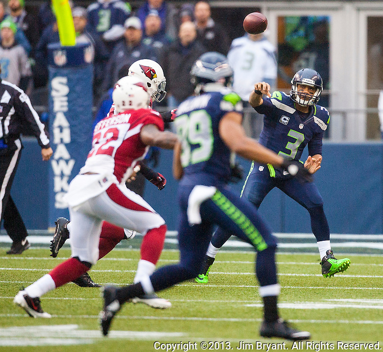 Seattle Seahawks  quarterback Russell Wilson looks to pass to wide receiver Doug Baldwin (89) while scrambling against the Arizona Cardinals defense during the third quarter at CenturyLink Field in Seattle, Washington on December 22, 2013.   Wilson completed 11 of 27 passes for 108 yards and threw for one touchdown and had one pass intercepted in the Seahawks 10-17 loss to the Cardinals. ©2013. Jim Bryant Photo. ALL RIGHTS RESERVED.