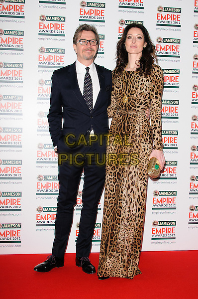 Gary Oldman and Alex Edenborough.The Jameson Empire Film Awards 2012, Grosvenor House Hotel, Park Lane, London, England..March 25th, 2012.full length suit brown dress leopard print married husband wife black white tie glasses goatee facial hair .CAP/CJ.©Chris Joseph/Capital Pictures.