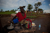 "Lomo Rama Abora , mother of 6, prepares breakfast with her children in Nyori refugee camp. Her where kidnapped by the LRA. "" They started to tie my children with rope. After they tied them they pulled them like goats into the forest."""