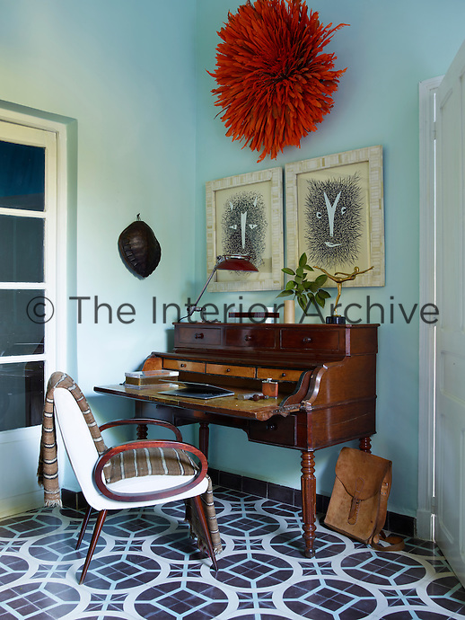 An 1820 Cuban desk from a Paris flea market and a French Art Deco armchair in the study. The drawings are by Roger Sandes and the feather headdress is from Cameroon.